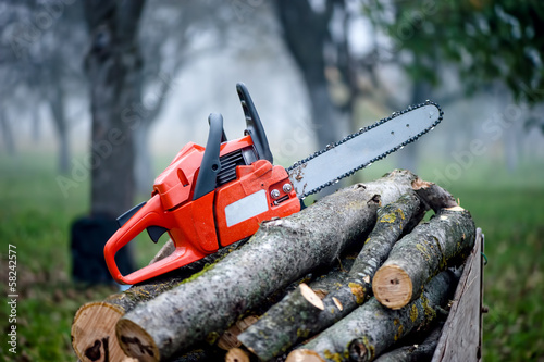 gasoline powered professional chainsaw on pile of cut wood - 58242577