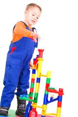 Kleiner Junge spielt mit Murmelbahn