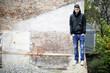 junger Mann steht auf einer Mauer