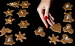 Woman lays gingerbreads on the baking tray by christmas time