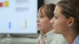 two women speaking at office meeting during presentation