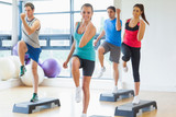 Fototapety Instructor with fitness class performing step aerobics exercise