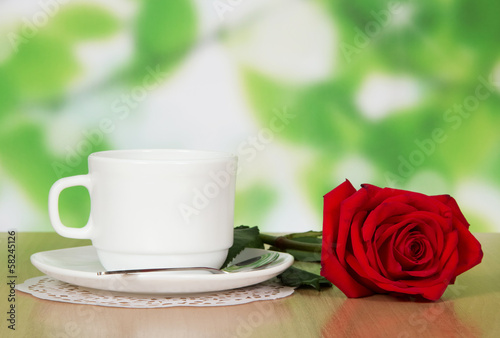 Cup of coffee with a red rose