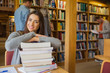 Female student with stack of books while others in background at