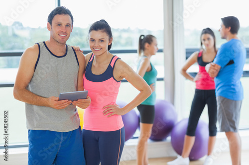 Fit couple holding digital table with friends chatting in backgr