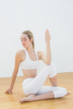 Concentrating ponytailed woman stretching her body sitting on fl poster