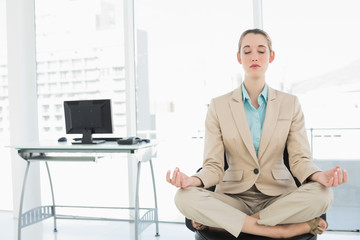 Concentrated calm businesswoman sitting in lotus position on her