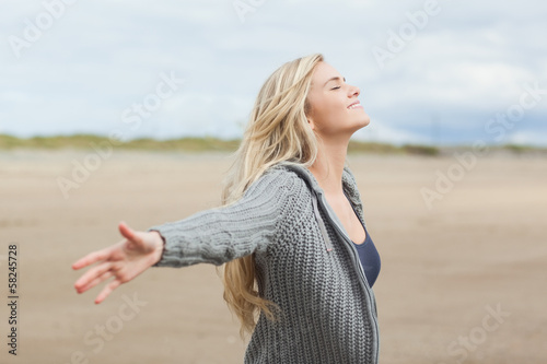 Side view of a woman stretching her arms on beach