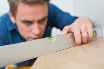 Young handyman using a spirit level