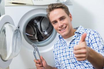 Technician repairing washing machine while gesturing thumbs up