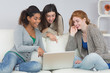 Cheerful female friends using laptop together at home