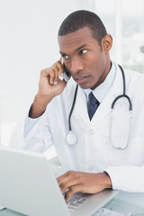 Concentrated male doctor using cellphone and laptop