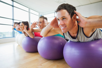 Side view of class exercising on fitness balls in a row