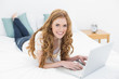 Smiling casual blond using laptop in bed
