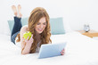 Blond using tablet PC while holding an apple in bed