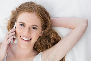 Cheerful young woman using mobile phone in bed
