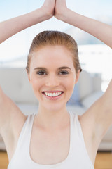 Smiling woman with joined hands over head