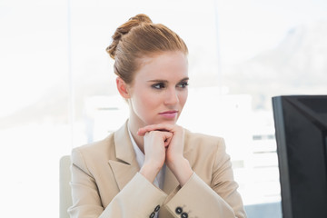 Worried young businesswoman looking at computer