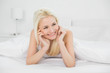 Close up of smiling beautiful blond lying in bed