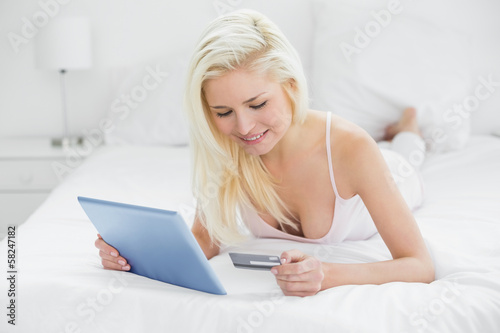 Casual young blond doing online shopping in bed