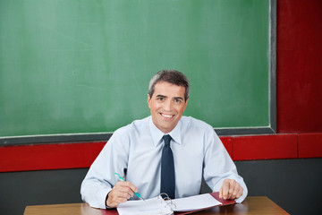 Happy Teacher With Binder And Pen Sitting At Desk