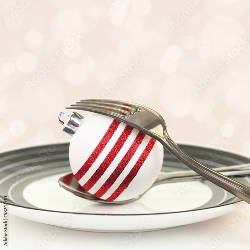 Christmas table setting with ornament on a plate
