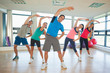 Full length of people doing power fitness exercise at yoga class