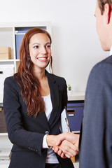 Handshake with businesspeople in office