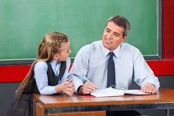 Male Teacher Looking At Schoolgirl In Classroom