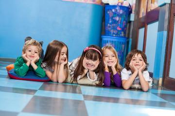 Boys And Girls Lying On Floor In Kindergarten