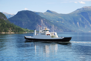 Ferry on blue water of Norwegian fjord.