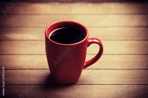 Red cup of coffee on wooden table