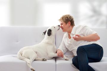 Frau mit Hund auf dem Sofa