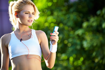 woman in white  sports bra rests while adjusting music on porta
