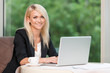 Smiling beautiful blond business woman with laptop.