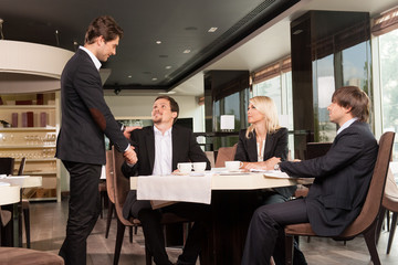 Group of  business people greeting  handsome businessman.