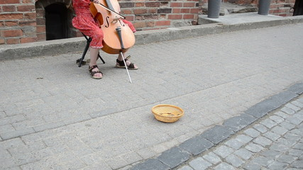 girl play with violoncello in oldtown. wicker dish money