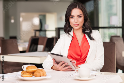 Attractive woman looking at camera while sitting at restaurant.
