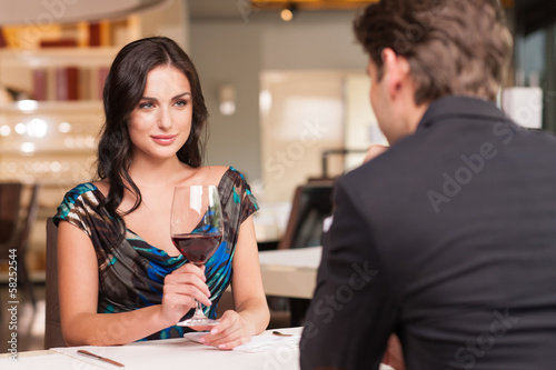 Seducing beautiful woman looking at her lover with wine glass.