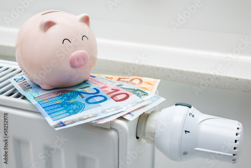 canvas print picture Heating thermostat with piggy bank and money