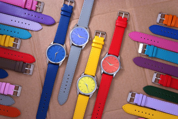 composition of colourful watches on cardboard background