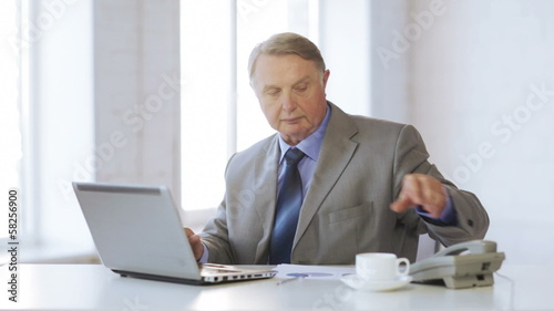 old man with laptop computer taking a phone call
