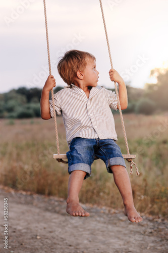 Happy young boy playing on swing in a park