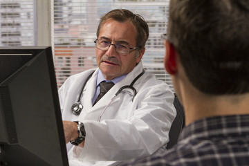 Doctor using computer while consulting with his patient
