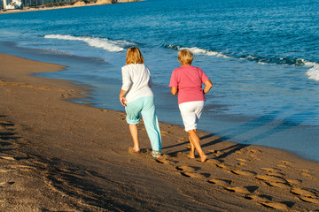 Rear view of women jogging on beach.