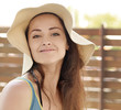 Beautiful smiling woman in hat looking happy outdoors. Closeup c