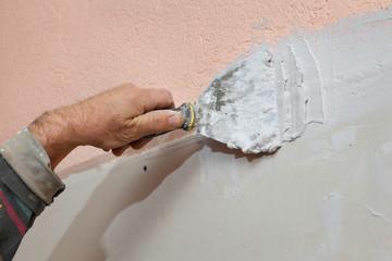 Worker spreading plaster with trowel to gypsum board, fiber mesh