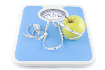 apple and measuring tape on the floor scales i