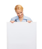 smiling female doctor or nurse with blank board