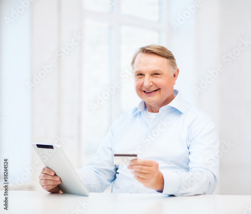 old man with tablet pc and credit card at home